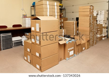 Small warehouse with cardboard boxes - stock photo