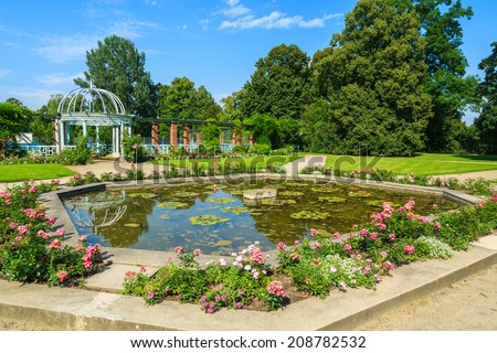 Small water pond in rose gardens of beautiful Lancut castle on sunny summer day, Poland - stock photo