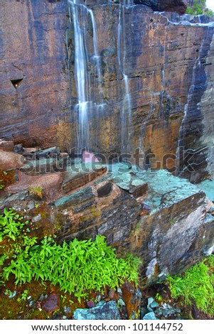 Small waterfall across a trail through the Many Glacier area of Glacier National Park - stock photo