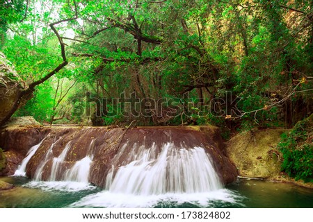 Small waterfall among green trees and bushes in the long-term recording - stock photo
