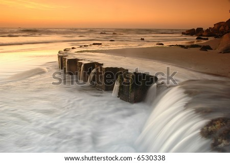 Small waterfall by the sea - stock photo
