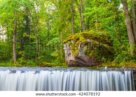 Small waterfall (cascade) on river with big stone, motion blur. Lahemaa national park, Estonia - stock photo