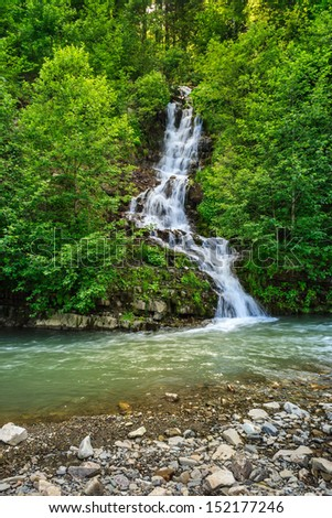 small waterfall coming out of the forest falls to a small mountain stream - stock photo