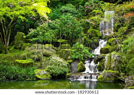 Small waterfall flowing into a koi pond in a Japanese garden. - stock photo
