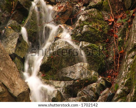 Small waterfall in forest - stock photo