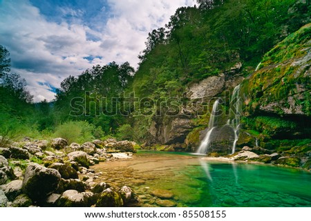 Small waterfall in mountain forest and turquoise lake under blue sky with clouds. - stock photo