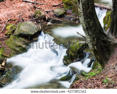 small waterfall of mountain river among the trees - stock photo