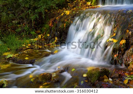 small waterfall with autumn leaves in flowing water - stock photo