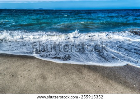 small waves by the shore in Platamona in hdr tone mapping effect - stock photo