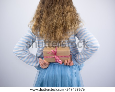 small wavy haired girl holding a present wrapped in brown paper with a check ribbon behind back - stock photo