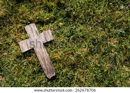 Small weathered cross on a background of grass and moss with copy space - stock photo