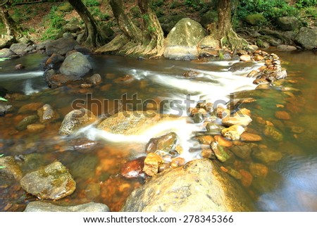 Small weir in mountain river. Big red boulders are sticking out from water with wet mossy carpet. Fresh colors of and white milky water below stones - stock photo