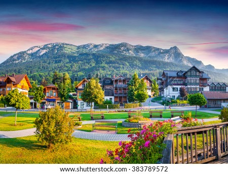 Small welcoming village Archkogl in the morning mist. Park on the near Grundlsee lake with beautiful summer flowers. Alps, Austria, Europe. - stock photo