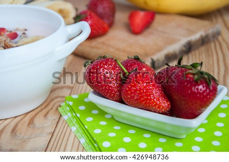 Small white bowl filled with fresh ripe red strawberries and bananas on an old wooden textured table with green fabric - stock photo