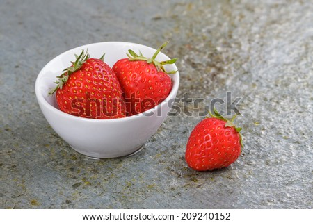 Small White China Bowl Filled with Fresh Ripe Strawberries on a Wet Slate Board. - stock photo