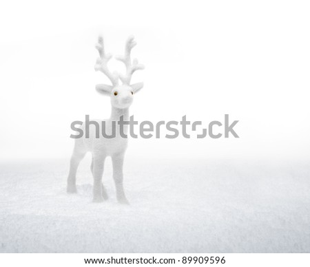 small white deer (ornament) standing in the snow, looking up. white background copy space