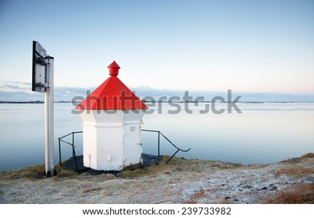 Small white lighthouse with solar panel at rocks at Helgeland coast, Norway. Light snow on ground. - stock photo