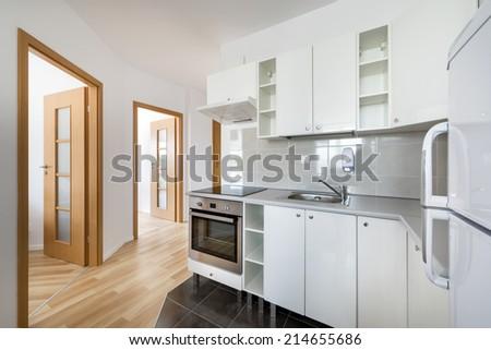 Small, white modern kitchen interior design in small apartment - stock photo