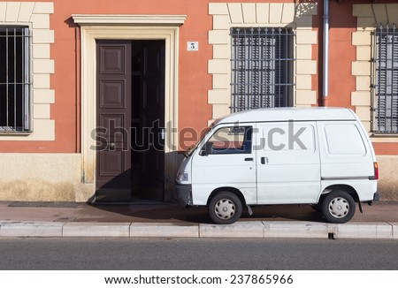 Small white van parked on a sidewalk or pavement