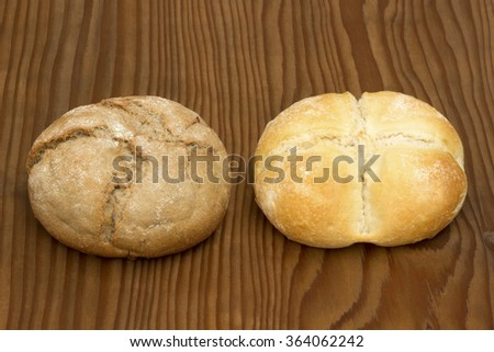 Small whole wheat  bread  and small white bread on old wooden table. - stock photo