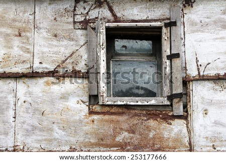 Small window of old rusty barn - stock photo
