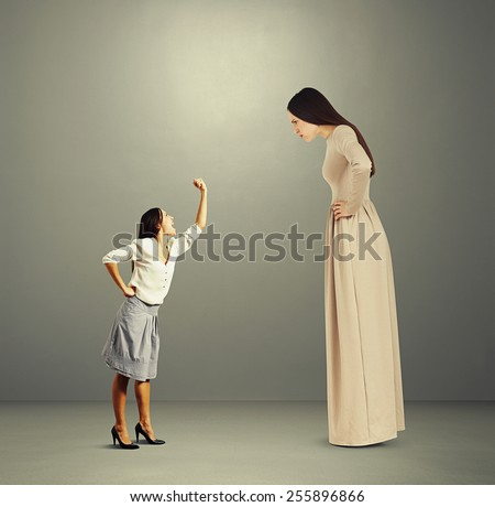 small woman screaming and showing fist to big angry woman over dark background - stock photo