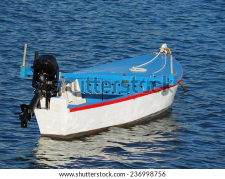 small wooden barge boat with outboard engine floats through blue lagoon waves                 - stock photo