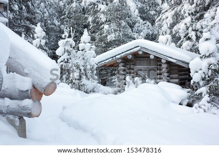 Small wooden blockhouse in winter under the white snow in the snowy forest of pine trees, winter landscape - stock photo