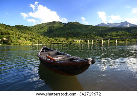 Small wooden boat on the Lang Co Bay, where you can see the bridge on Ah1 Road across the Lang Co Bay to the Hai Van Tunnel, connect Hue and Danang Vietnam.