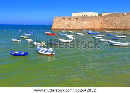 Small wooden boats near the walls of Santa Catalina Castle in Cadiz, Andalusia, Spain - stock photo