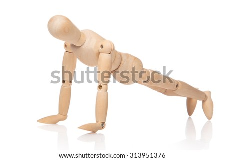 Small wooden dummy during push ups on white background