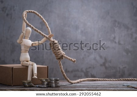 Small wooden dummy sitting with hangman's noose and coins over the grey concrete wall - stock photo