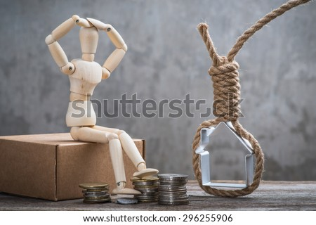 Small wooden dummy sitting with hangman's noose, house and coins over the grey concrete wall - stock photo