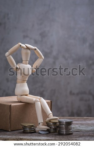 Small wooden dummy with coins over the grey concrete wall - stock photo