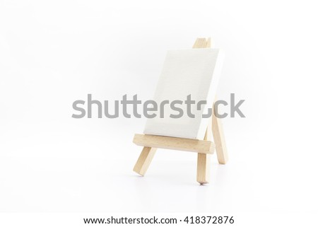 Small wooden easel with canvas with blank space ready for your advertising isolated on white background.