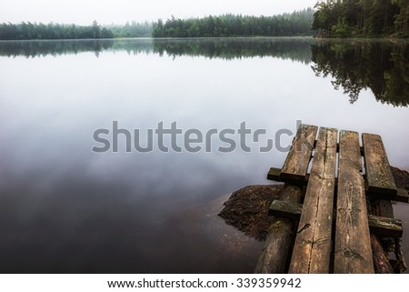 Small wooden foot-bridge in forest lake an early fall morning - stock photo