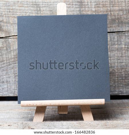 Small wooden framed blackboard on wooden background
