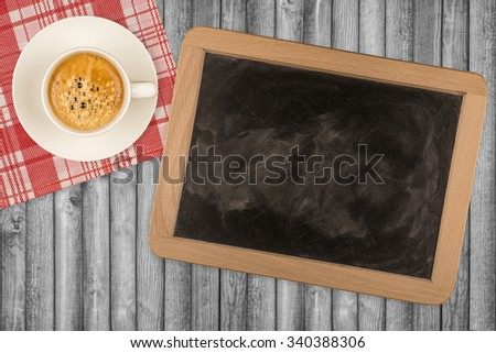 Small wooden framed blackboard with cup of coffee on wooden background - stock photo