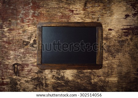 Small wooden framed blank chalkboard on a old dark background - stock photo