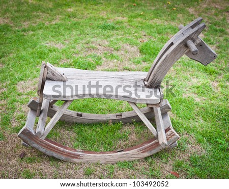 Small wooden horse on grass - stock photo