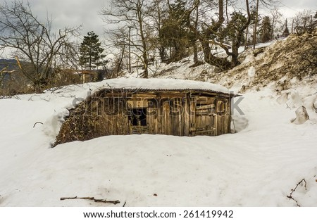 Small wooden house in the snow in winter forest - stock photo