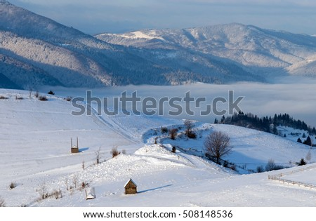 Small wooden house on a snowy hill in the mountains at dawn. Winter landscape.