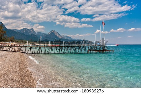 Small wooden pier on shingle beach and aquamarine water in popular touristic resort of Kemer on Mediterranean sea in Turkey. - stock photo