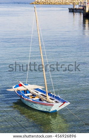 Small wooden sailboat anchored on Cangas de Morrazo harbor