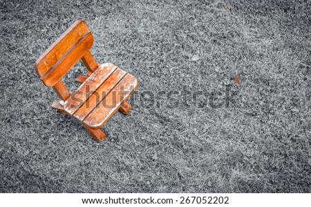 Small wooden stool with selective color on black and white field of grass - stock photo