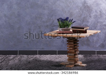 Small wooden table, books and lavender on grey wall background - stock photo