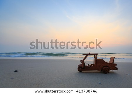 Small wooden toy car (Tuk Tuk Thailand) on beach - stock photo