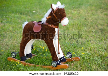 Small wooden toy horse on the grass - stock photo