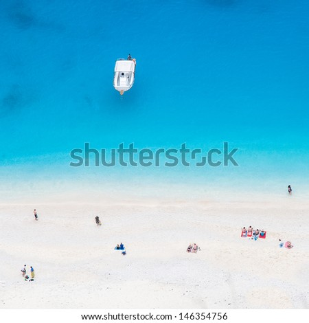 small yacht anchored near white beach full of holidaymakers - stock photo