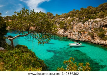 small yacht floating in azure sea in the village Cala Pi, Majorca, Spain - stock photo